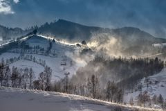 Romanian hillside and village in winter time , mountain landscape of Transylvania in Romania. With frost and blizzard royalty free stock image
