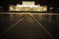 Romanian House of Parliament. A night view across an open square toward the brightly illuminated House of Parliament in Bucharest, Romania Royalty Free Stock Photos