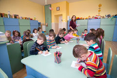 Romanian kindergarten. Children from a Romanian kindergarten drawing With the teacher watching them Stock Images