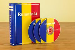 Romanian language textbook with flag of Romania and CD discs on. The wooden table. 3D Royalty Free Stock Image