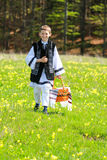 Romanian national port. Young boy dressed in Romanian national port carrying a traditional basket  on the beautiful green grass and full of dandelions Stock Photo