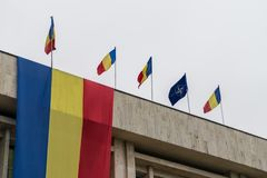 Romanian and NATO flags in the wind.  stock photography