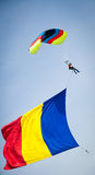Romanian Parachuter. Parachuter performing at an airshow carring and waving a huge romanian flag in the blue sky Royalty Free Stock Photos