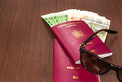 Romanian passports with Euro banknote and sunglasses on wood tab Royalty Free Stock Images