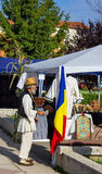 Romanian peasant in a fair. Looking at the flag Royalty Free Stock Photos
