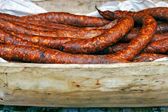 Romanian sausage in a rustic wooden bowl carved Stock Photography