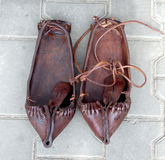 Romanian shoes. Ancient traditional Romanian shoes on concrete background Stock Photos