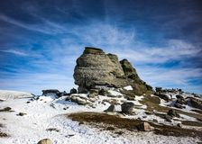 Romanian Sphinx dolomite in Bucegi. Scenic view of the Sphinx of Romania in the Bucegi mounatins during winter with little snow and blue sky royalty free stock photo