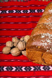 Romanian sponge cake and bunch of walnuts on red traditional tow Stock Photography