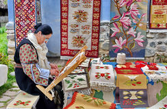 Romanian traditional rug. Romanian woman working at traditional carpet woven with colored wool royalty free stock photos