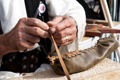 Romanian traditional sandal making. At a local fair in Craiova, Romania many craftsmen were invited. Some were dressed in national traditonal clothing and Royalty Free Stock Photography