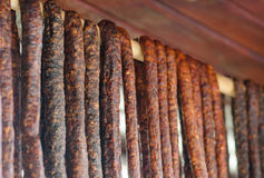 Romanian traditional sausages hanging on a wood stick Royalty Free Stock Images