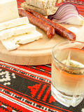Romanian traditional snack of cheese onion sausages bread and plum brandy on a wooden plate Stock Photo