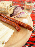 Romanian traditional snack of cheese onion sausages bread and plum brandy on a wooden plate Stock Photos