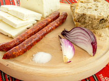 Romanian traditional snack of cheese onion sausages and bread on a wooden plate Royalty Free Stock Photography