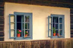 Romanian traditional wooden house with old blue windows and flow. Ers, close view Royalty Free Stock Images