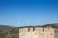Romanian Wind Farm with Wind Turbine and windmills facing an old castle located on the Serbian side of the Danube river. Picture of a Wind Farm located on the royalty free stock photo