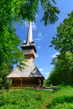 Romanian wooden church with far airplane in the sky. Stock Photos