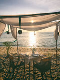 Romanic dinner on the beach. Old fashion retro styled photo.  Stock Photo