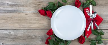 Romanic dinner table setting for the holiday season. Holiday Dinner setting with red roses and silverware on rustic wood in flat lay view Stock Image