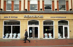 Romans Estate Agents. Reading, England - April 23, 2015: A man walks by a Romans Estate Agents window display in Reading, England. According to the Nationwide Royalty Free Stock Photo