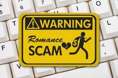 Romanskt Scam varningstecken på ett tangentbord Arkivfoto