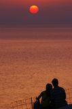 Romantic. A man and his girl friend are watching the sunset in Santorini, Greece stock image