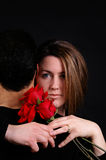 Romantic. A woman hugging her husband holding roses royalty free stock images