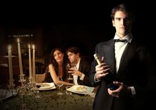 Romantic. Waiter with bottle of wine and a couple on the background Royalty Free Stock Image