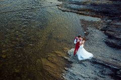 Romantic above portrait of the smiling newlyweds tenderly hugging at the river bank during the sunny day. stock photos