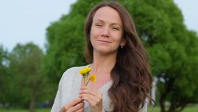 Romantic adult woman with small dandelions in countryside. Romantic adult woman with gentle dandelions flowers. Portrait of Happy smiling woman with long wavy stock video