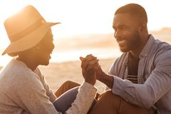 Romantic African couple sitting together on a beach at sunset. Close up of trendy young African couple sitting and holding hands together on a sandy beach while stock photos