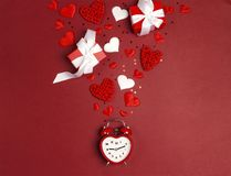 Romantic alarm clock with gifts and hearts on red background. Place for text. Top view, flat lay royalty free stock photos