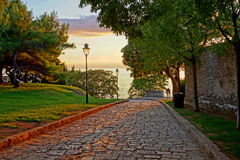 Romantic alley. Beautiful street with a couple and the sunset sea in the background Stock Photos