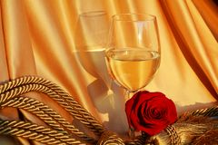 Romantic ambience. The juxtaposition of romantic elements like the red rose and the glass of wine having shiny golden folds of an elegant fabric in the back Stock Photo