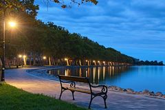 Free Romantic And Peaceful Scene. Empty Bench Illuminated By Lamppost. Morning Landscape View Of Lake Balaton And Plane Tree Alley Royalty Free Stock Image - 160900626