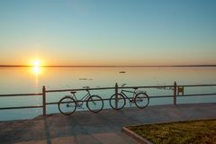 Romantic appointment at sunset. Men`s and female bicycles wait for lovers Royalty Free Stock Photo