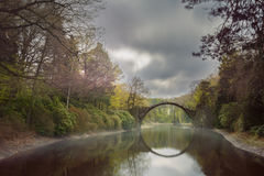 Romantic arch bridge. Rakotzbrucke also known as Devils Bridge in Kromlau is a romantic place in Germany, which was bulit in 1860. Reflection of the bridge in Royalty Free Stock Images