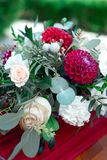 Romantic arrangement of red and white flowers. Romantic arrangement of red and white summer flowers with roses and dahlias on a matching red tablecloth with Royalty Free Stock Photography