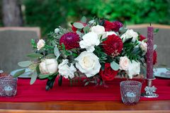 Romantic arrangement of red and white flowers. Romantic arrangement of red and white summer flowers with roses and dahlias on a matching red tablecloth with Royalty Free Stock Image
