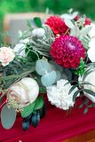 Romantic arrangement of red and white flowers. Romantic arrangement of red and white summer flowers with roses and dahlias on a matching red tablecloth with Stock Image