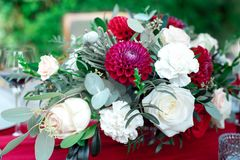 Romantic arrangement of red and white flowers. Romantic arrangement of red and white summer flowers with roses and dahlias on a matching red tablecloth with Stock Images