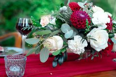 Romantic arrangement of red and white flowers. Romantic arrangement of red and white summer flowers with roses and dahlias on a matching red tablecloth with Stock Photography