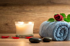 Romantic arrangement with scented candle and rose. Romantic spa arrangement with a burning white scented candle, red petals, two black stones and a rose on a Royalty Free Stock Photo