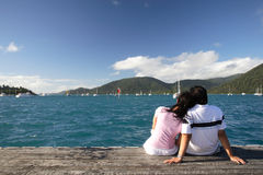Romantic Asian couple on the beach. Asian couple enjoying the beautiful sea landscape while sitting on a piece of wood Stock Image
