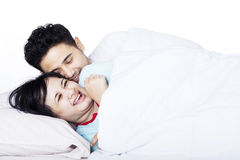 Romantic Asian couple in bed - isolated Royalty Free Stock Images