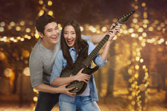 Romantic asian couple of lovers playing guitar Stock Image