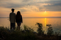 Romantic Asian couple standing together on bank of lake at sunrise or sunset Royalty Free Stock Image