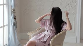 Romantic asian fashion model posing sitting on chair in studio interior stock video footage
