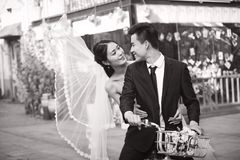 Romantic asian newly-wed riding a bicycle royalty free stock photos